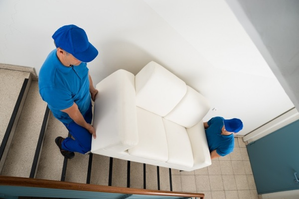High Angle View Of Two Male Movers Carrying Sofa On Staircase Of House